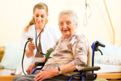 a nurse checking the blood pressure of senior woman